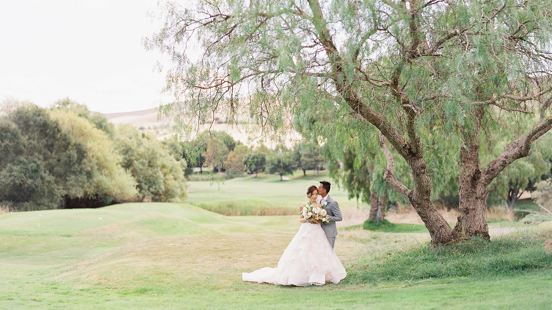 A couple share a beautiful moment under a tree at Hiddenbrooke Golf Club in Vallejo